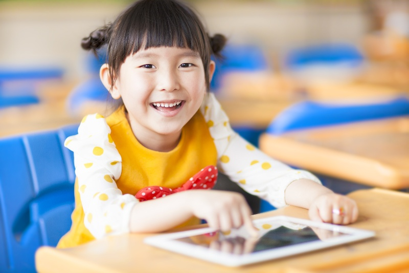 Girl in class with mobile device