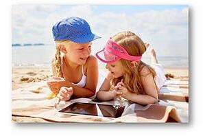 Kids on the beach with a digital device